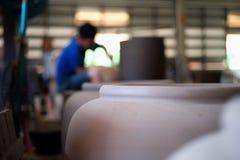 Kleikruiken in productielijn met vage arbeider op achtergrond bij de aardewerkfabriek Vakmanschap en met de hand gemaakt product stock afbeeldingen