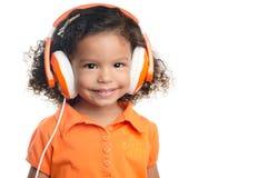 Klein afro Amerikaans meisje met heldere oranje hoofdtelefoons Stock Foto's