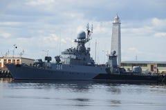 Klein anti-submarine schip Urengoy op de achtergrond van de oude houten vuurtoren Kronstadt Stock Foto