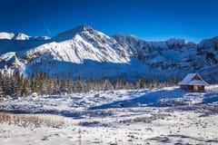 Klein bergplattelandshuisje in het hooggebergte in de winter Stock Fotografie