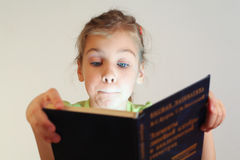 Klein blauw ogenmeisje gelezen boek Stock Afbeeldingen