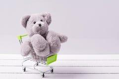 Klein boodschappenwagentje en een teddybeer Conceptueel beeld voor verkoop van speelgoed of de fantasieën van kinderen Stock Afbeeldingen