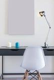 Klein bureau met witte stoel en enige lamp Stock Afbeelding