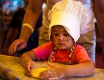Klein chef-kokjong geitje die eigengemaakte cake met moeder op keuken koken Royalty-vrije Stock Foto
