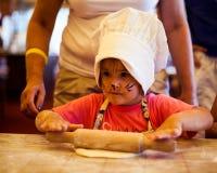 Klein chef-kokjong geitje die eigengemaakte cake met moeder op keuken koken, die deegrol voor deeg met behulp van Stock Foto