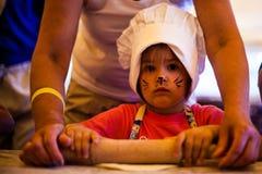 Klein chef-kokjong geitje die eigengemaakte cake met moeder op keuken koken, die deegrol voor deeg met behulp van Royalty-vrije Stock Fotografie