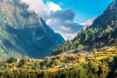 Klein die dorp op de heuvel door een zonnestraal tegen bergen wordt aangestoken royalty-vrije stock afbeelding