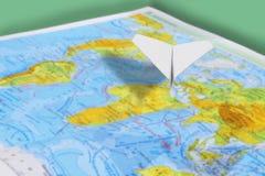 Klein document vliegtuig over een geografische kaart van de wereld Selectieve nadruk royalty-vrije stock foto