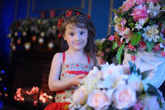 Klein donker-haired meisje in een rode kleding naast de bloemen in een vaas Stock Afbeeldingen