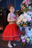 Klein donker-haired meisje in een rode kleding naast de bloemen in een vaas Royalty-vrije Stock Foto's