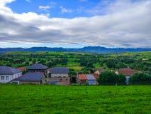Klein dorp in midden van een vallei rond de bergen en gre stock afbeeldingen
