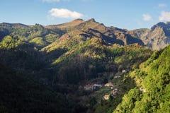 Klein dorp onder de bergen met groen bos Stock Afbeelding
