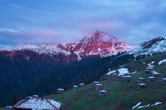 Klein dorp onder een snow-covered bergrand tijdens zonsondergang Royalty-vrije Stock Afbeelding