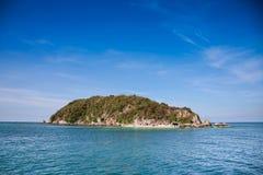 Klein eiland in het midden van het overzees en de blauwe hemel Stock Foto