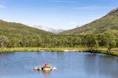 Klein eiland met model van een vissers` s huis in een meer op Lofo stock foto's