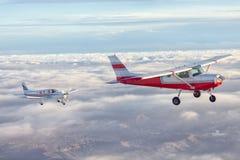 Klein enig motorvliegtuig die in de schitterende zonsonderganghemel door het overzees van wolken boven de spectaculaire bergen vl royalty-vrije stock foto's