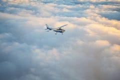 Klein enig motorvliegtuig die in de schitterende zonsonderganghemel door het overzees van wolken vliegen stock afbeelding