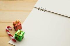 Klein giftvakje, klein riet en lege document pagina gezet op houten bac Royalty-vrije Stock Foto's