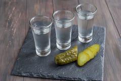 Klein glas met Russische wodka en zoute komkommer Stock Foto's