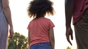 Klein goedgekeurd meisje die zich tussen twee nieuwe ouders, bang te houden en te vertrouwen bevinden op stock afbeelding