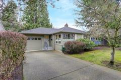 Klein grijs huis buiten met een garage royalty-vrije stock afbeelding