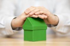 Klein groen die huis door handen wordt beschermd Stock Afbeelding
