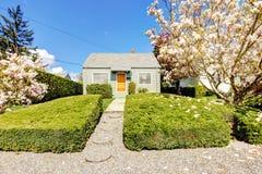 Klein groen huis buiten met de lente bloeiende bomen. Stock Foto