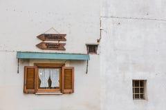 Klein houten venster met twee pijlen die aan de kerk en t richten Stock Foto