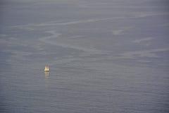 Klein jacht op de oceaan stock foto