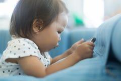 Klein jong geitje dat teveel tijd lettend op TV aan een mobiele telefoon doorbrengt stock afbeelding