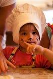 Klein jong geitje die eigengemaakte cake in een keuken met het art. van het kattengezicht koken Royalty-vrije Stock Foto