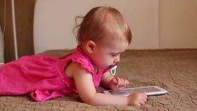 Klein jong geitje die op bank liggen en met tablet spelen stock footage