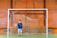 Klein jongens speelvoetbal op een binnenhof royalty-vrije stock foto's