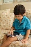 Klein kind die een digitale tablet gebruiken Stock Foto