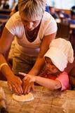 Klein kind die eigengemaakte cake met grootmoeder op keuken koken Stock Afbeelding