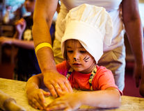 Klein kind die eigengemaakte cake met moeder op keuken koken Stock Afbeelding