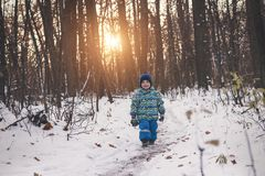 Klein kind die op een sneeuwweg onder somber bos lopen stock afbeelding
