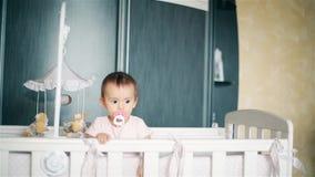 Klein kind die zich in bed met een uitsteeksel in zijn mond HD bevinden stock video