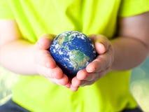 Klein kind in een groene T-shirt die de aarde in haar handen houden De Dag van de aarde Groen concept royalty-vrije stock afbeelding