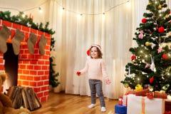 Klein kind in santahoed bij Kerstmis in de verfraaide ruimte smil Stock Foto