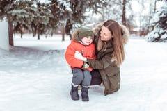 Klein kind van 3-5 jaar oud, de jongenswinter in warm jasje en hoed In de winter, in sneeuw tegen een achtergrond van groen stock fotografie