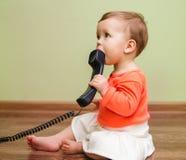 Klein leuk babymeisje met telefoon op de vloer Stock Foto's
