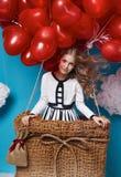 Klein leuk meisje die op rode de Valentijnskaartendag van hartballons vliegen Royalty-vrije Stock Fotografie