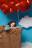Klein leuk meisje die op rode de Valentijnskaartendag van hartballons vliegen Royalty-vrije Stock Afbeelding