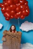 Klein leuk meisje die op rode de Valentijnskaartendag van hartballons vliegen Royalty-vrije Stock Afbeeldingen