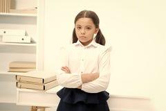 Klein maar ernstig Het kindmeisje draagt school eenvormige status met gekruiste wapens op borstschoolmeisje het slimme kind kijkt stock fotografie