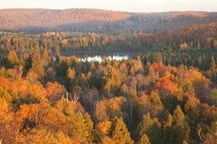 Klein meer onder heuvels en bomen met dalingskleur in noordelijk Minnesota stock foto's