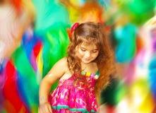 Klein meisje dat over de achtergrond van onduidelijk beeldkleuren danst Stock Foto