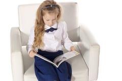 Klein meisje die een boek lezen en op de stoel zitten Schoolmeisje op witte achtergrond wordt geïsoleerd die Hoogste mening Royalty-vrije Stock Foto's