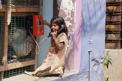 Klein meisje die een telefoongesprek in landelijk India maken Stock Foto's